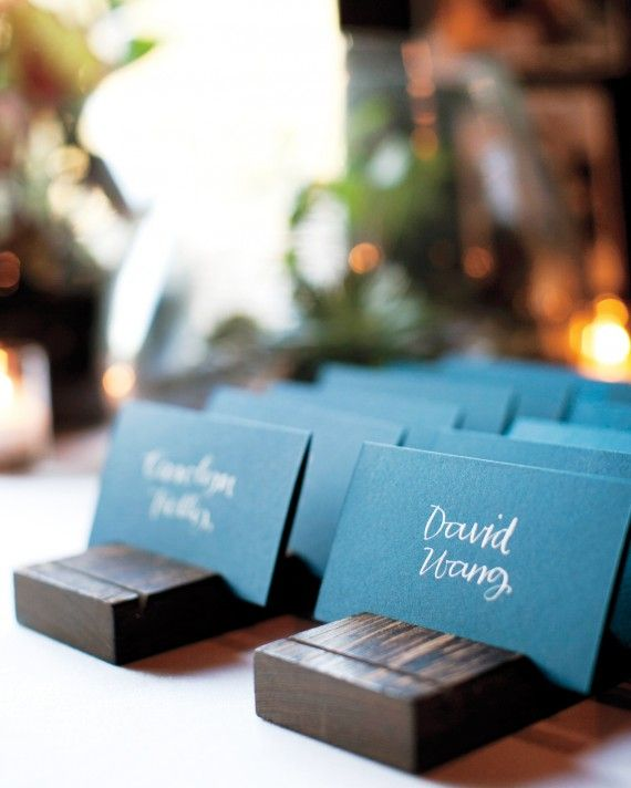 Guests' names and table numbers are propped up in stained-oak holders for a simple yet sophisticated look.