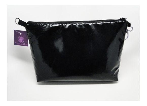 Divisória para bolsa na cor preta, forrada e acolchoada, feita em tecido tipo vinil por fora e tecido de algodão por dentro. Fechamento por zíper. Vem com uma argola em uma ponta e um mosquetão na outra ponta, para prender à sua bolsa, deixando tudo organizado dentro dela. Ideal para bolsas grandes que não têm fecho! Serve também como uma necessaire tamanho grande, para levar tudo o que você precisa!