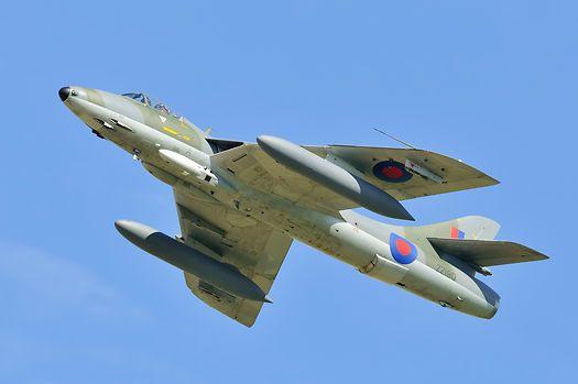 A Hawker Hunter F58 in flight from below with a blue sky backdrop.