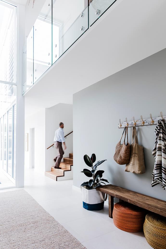 Rob makes his way up the spotted-gum steps. Above him, a glass balustrade allows extra light into the upstairs hallway.  Photo: Maree Homer | Styling: Rebecca Fuge | Story: Australian House & Garden