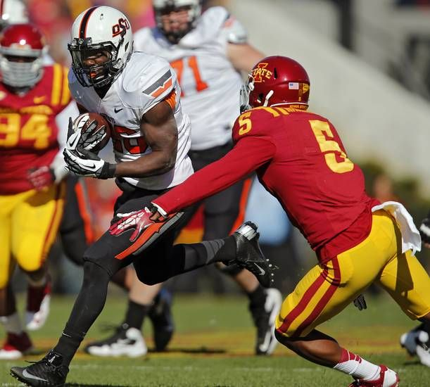 Oklahoma State 's Desmond Roland (26) runs past Iowa State's Jacques Washington (5) during the college football game between the Oklahoma State University Cowboys (OSU) and the Iowa State University Cyclones (ISU)