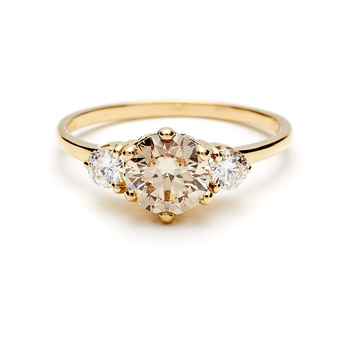 """Brides.com: 71 Engagement Rings with Colorful Stones. 3 stone """"Hazeline"""" 14K yellow gold with 1.2 carat champagne diamond center and white diamond side stones, $10,500, Anna Sheffield  See more round-cut engagement rings."""
