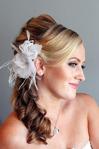 This is one of the very many wedding hairstyles for long hair that appears medium in length due to its tightly curled side swept ponytail.