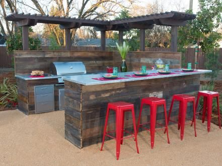 After: A beautiful barbecue island is the highlight of the backyard makeover. Featuring an amazing barbecue station made with reclaimed wood, with a built-in refrigerator and gas barbecue with zinc countertops.