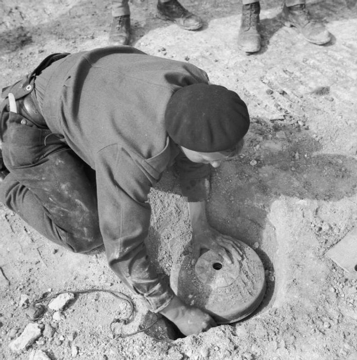 A sapper of 8th Field Squadron Royal Engineers lifts a mine on the Thala-Kasserine road, 24 February 1943.