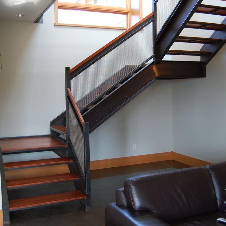 Escalera y barandilla de acero ennegrecido.  El relleno es malla de alambre tejido de acero inoxidable.  Diseñado por los objetos formados.