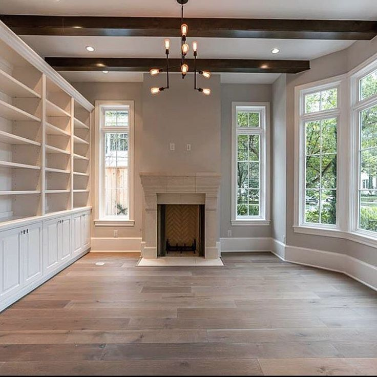 """A stunning study on a Saturday morning #CroixCustomHomes"" French white oak floors. Herringbone. White built-ins. Industrial chandelier. Thick baseboards."