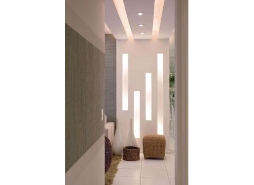 """Com 15 cm de profundidade, o nicho de gesso vertical cria uma delimitação entre as salas de estar e de jantar. A mesma ideia foi utilizada para o teto, criando uma iluminação indireta com intensidades de luz em tons amarelados. Para chegar a esse efeito, foram usadas lâmpadas minidicroicas de 35 w nos rasgos da parede e """"bolinhas"""" de 7 w para o teto."""