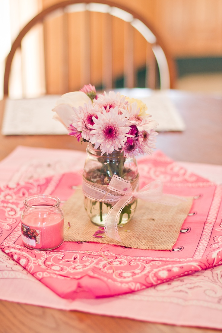 Simple pink bandanas (Michaels) with a piece of burlap on it (Amazon), a mason jar wrapped with a strip of burlap and ribbon, and some assorted flowers.  These were the table centerpieces. #vintagecowgirl #cowgirlparty