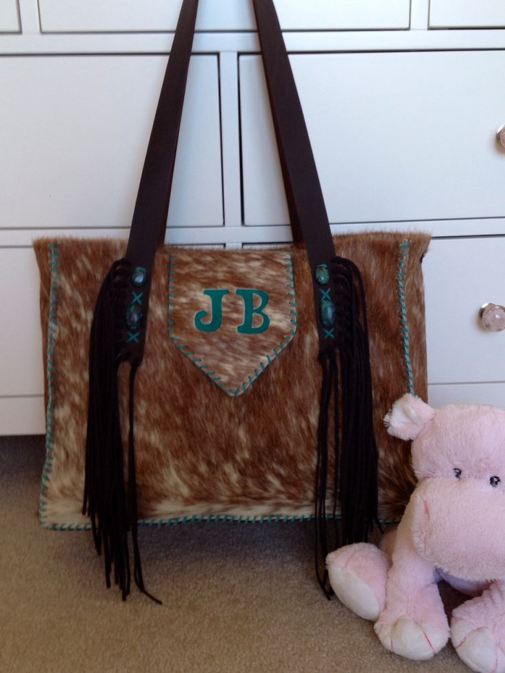 A Buckaroo Diaper Tote, customized with the customers initials in turquoise suede. Made to order cowhide bags from gowestdesigns.us