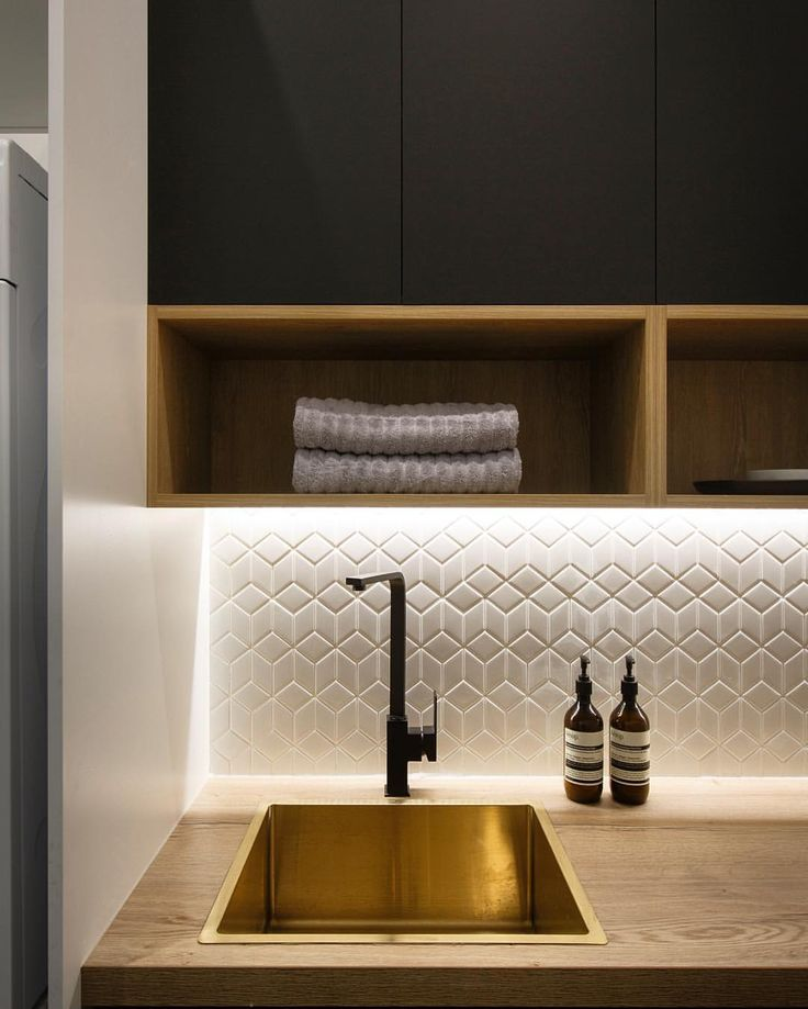 hexagonal splashback; brass sink; black brassware; black/ anthracite grey & natural timber cabinets; contemporary utility room; open wall Kitchen shelves