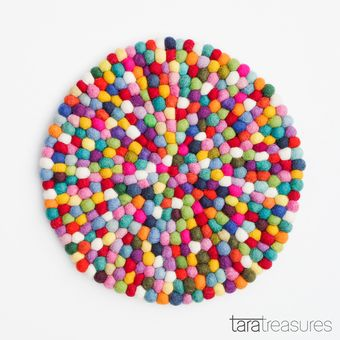 Colourful pot trivet made of wool felted balls. Beautiful and functional, this colourful felt ball pot trivet is made to withstand heat without damaging your tabletop. #feltballcoaster