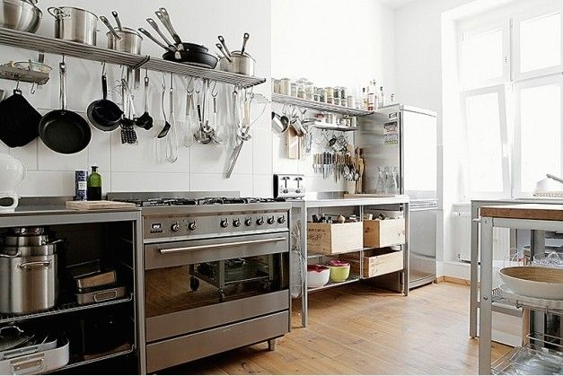 A Berlin kitchen via Behomm with modular stainless components and crates as storage.