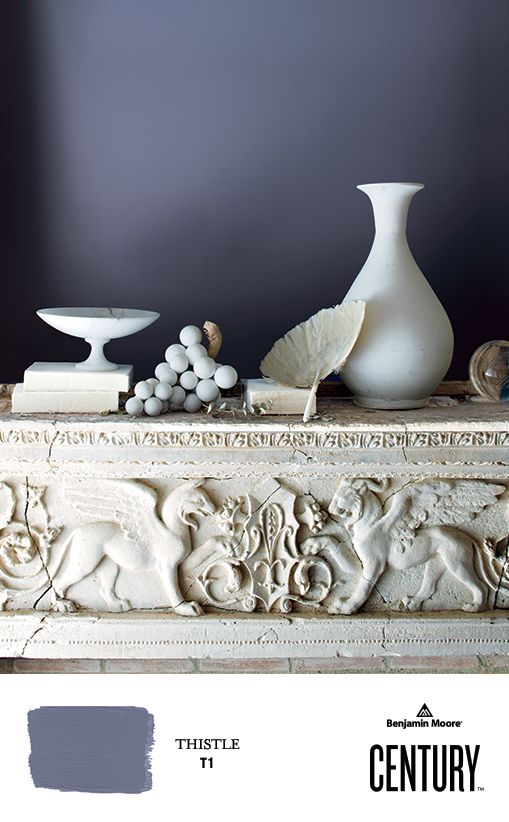 A collection of unglazed ceramics adorn an ornate marble mantel, contrasted by a wall painted in THISTLE T1, CENTURY Soft Touch Matte. #ExperienceCENTURY #BenjaminMoore