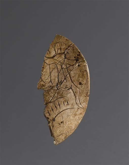 Rondelle découpée en os figurant sur chaque face un homme attaqué par une patte d'ours, provenant de la Grotte du Mas d'Azil (Ariège). Fait partie de la collection E. Piette. © RMN-GP (MAN) / T.Le Mage