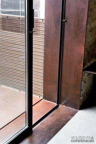 Chapas de corten cobrem o piso da varanda e o marco da porta de correr. É do mesmo material a malha vazada de proteção, que fecha a estrutura de aço inox no parapeito da varanda. Projeto da arquiteta espanhola Anna Noguera.