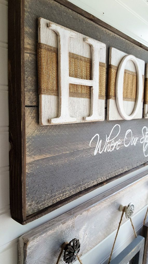 This beautiful sign is made of rough sawn pine, sanded, painted and distressed for a warm rustic look. The hand cut letters H-O-M-E are painted white and mounted to white antiqued square boards with a deep gold linen look ribbon. Need a different color? Just ask and we can coordinate whatever colors youd like. Approx. size: 28*1/2W X 11-3/4H Back is made of luan with two slotted hangers for easy wall display. You have the option to buy the picture hanger with 4 frames and the HOME s...