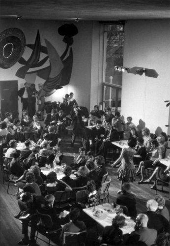 Modeshow (Zazieshow) in het restaurant van het Stedelijk Museum in Amsterdam, mode voor de jonge tiener, vanaf 9 jaar. Gasten en persfotografen richten hun blik|camera op het meisje dat in een mouwloze jurk met stroken tussen de tafels doorloopt. Achterin een muurschildering van Karel Appel. 1961.