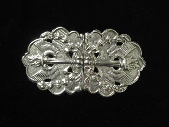 Beautiful stamped out silver Art Nouveau revival belt buckle. Hallmarked with the lion sterling mark, the buckle has been decorated with centrally placed winged torches, with a bow tied round the base and laurels shooting round the sides. It reminds one of icons used around the Olympic Games of the early 20th Century.