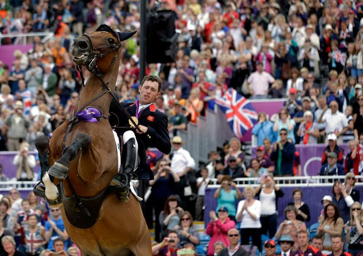 Hello Sanctos, the horse ridden by Scott Brash, of Great Britain, rears as the crowd cheers during a victory lap after Great Britain won the gold medal for the equestrian team show jumping at the 2012 Summer Olympics, Monday, Aug. 6, 2012, in London. (AP Photo/David Goldman)