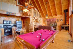 A living room with a pool table at a cabin in the Smoky Mountains.