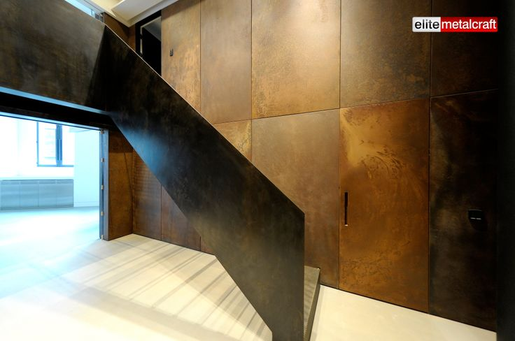 "Staircase was constructed using a custom made perforated folded steel sheet with a solid steel plate for balustrade, all with our in house ""Gun Metal"" surface finish. Decorative wall panels cleverly positioned to act as doors and secured without any visible fixings. Corroded natural Cor-ten steel panels gives a totally natural look to this amazing interior fit out."