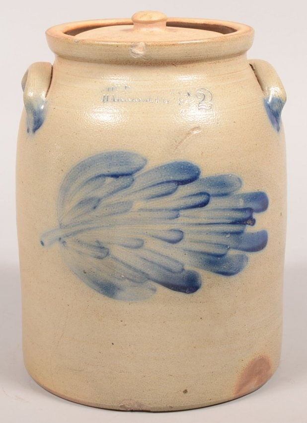 """Sold $ 200 Cowden & Wilcox, Harrisburg, PA Leaf Decorated 2 Gallon Stoneware Crock. Circa. 1860-1887. Cobalt blue brushed slip of a single large leaf design. Ovoid form with molded rim and ear handles. 12"""" high with lid. Condition: Good with one edge chip."""