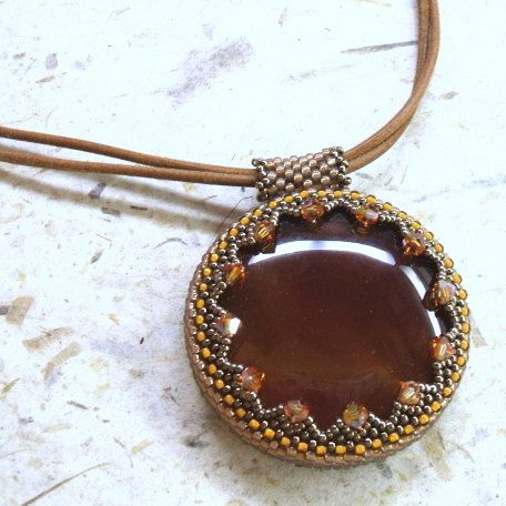 Leather necklace with woven bead embroidered carnelian pendant. A woven bead embroidery network of tiny seed beads in different shades of bronzy gold encases this fat round cabochon of beautiful carnelian.