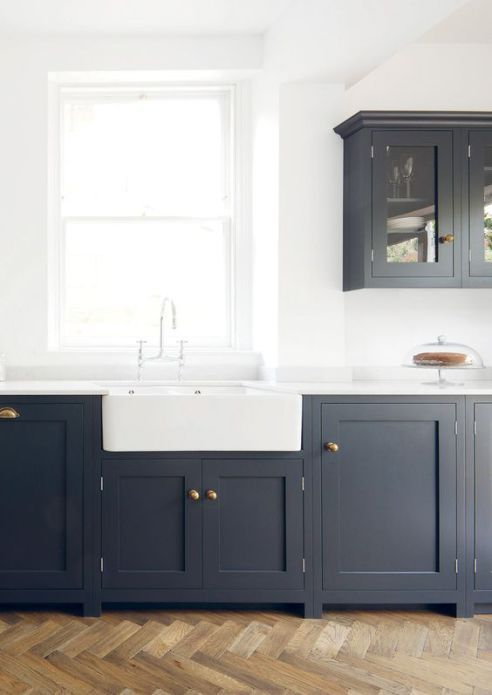 Navy kitchen cabinets with white walls, counters, and sink.