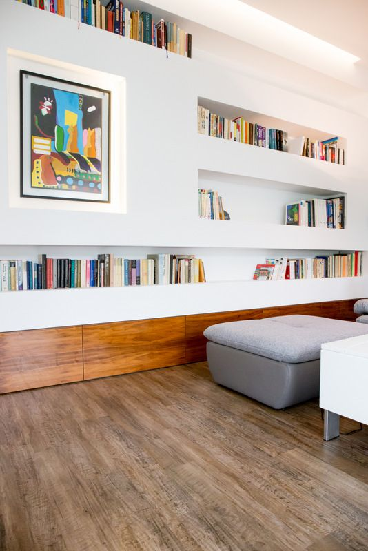Unusual living room furnishing -  inbuilt library shelving, light up niche for art work and bespoke bottom storage drawers made of walnut veneer in high gloss finish.