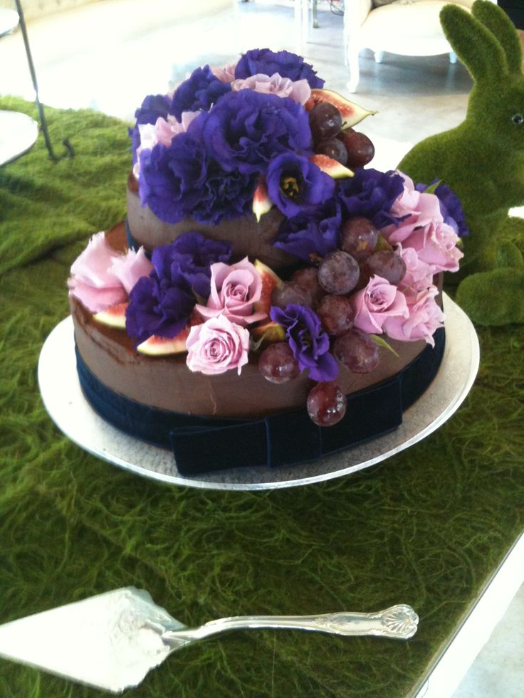 Purple flowers on chocolate wedding cake. For more wedding flower designs please go to www.naomijones.com.au.