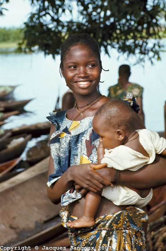 Smiling woman carrying baby along Ngiri River, Democratic Republic of the Congo (ex-Zaire).