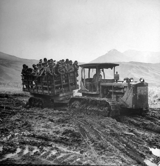 American troops are carted by tractor to the movies from an isolated camp in Massacre Valley, Attu Island, Aleutian Campaign, Alaska, 1943.