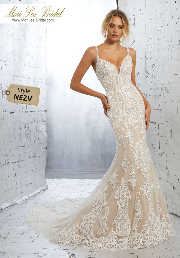 Style NEZV Kimora Wedding Dress Striking Deco Medallion Embroidery Accents and Trims This Sultry Fitted Net Gown. A Scalloped Hemline and Sheer Train Complete the Look. Available in Three lengths: 55″, 58″, 61″. Colors Available: Diamond White, Ivory/Nude