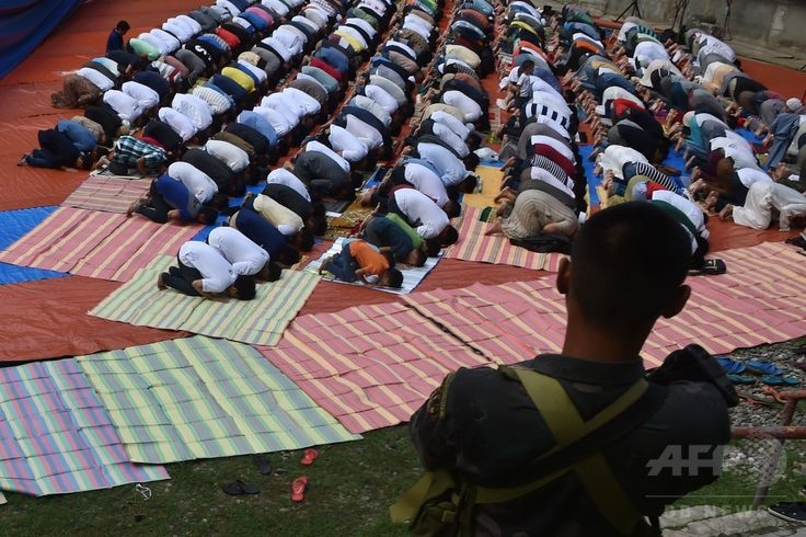 フィリピン南部ミンダナオ島 Mindanao  のイリガン市 Iligan で、イスラム教の断食月「ラマダン Ramadan 」の終了を祝う「イード・アル・フィトル Eid al-Fitr 」で祈る、マラウィ Marawi での戦闘を逃れてきたイスラム教徒の住民たちと、警備にあたる警察の特殊部隊(2017年6月25日撮影)。(c)AFP/Ted ALJIBE ▼25Jun2017AFP|フィリピン軍、ラマダン明けでマラウィでの戦闘を一時停止 http://www.afpbb.com/articles/-/3133328