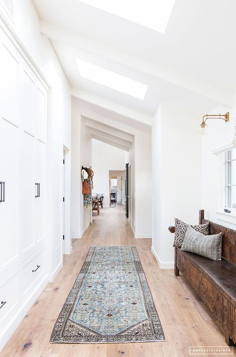 Angled ceiling, pale timber floors, dark bench seat and built in storage! This might be the best entry I've ever seen!!