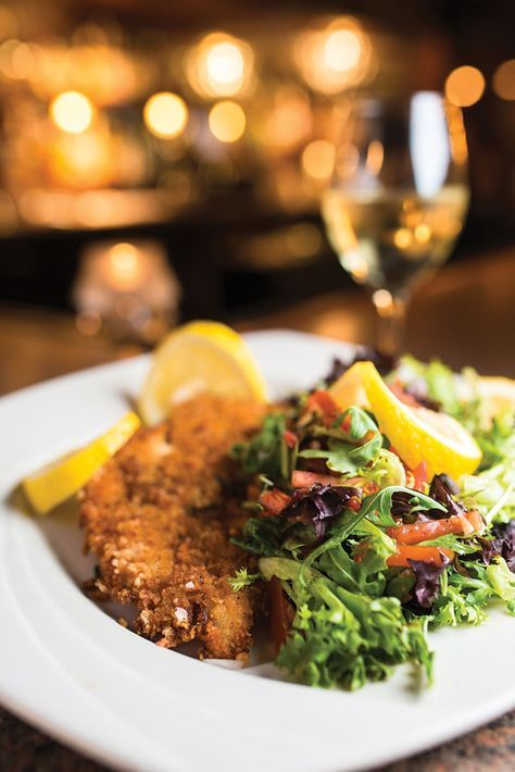 from deLorenzo's Italian Restaurant INGREDIENTS • 2 lbs. veal cutlets, cut in 4 oz. pieces • Oil for frying • Juice from 1/4 lemon • 2–4 cups fresh arugula or mixed baby greens Breading mixture • 4 cups plain breadcrumbs • 1/4 cup granulated...