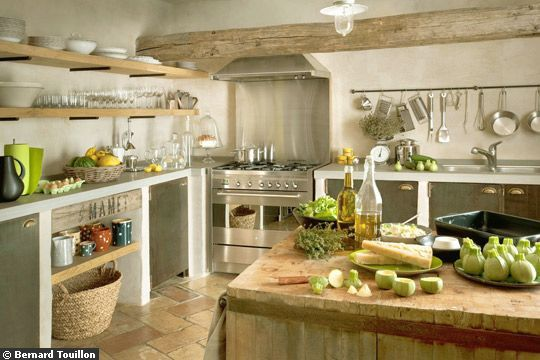 Look at this kitchen: sleek range and hood, all cooking utensils at hand, old wood block as island. Love the heavy wood beam also, and the stone floor.