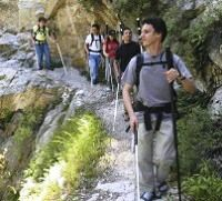 Photo of Daniel Kish, President of World Access for the Blind, leading a group of blind hikers along a steep mountain trail. Photo credit: Volker Correll for World Access for the Blind
