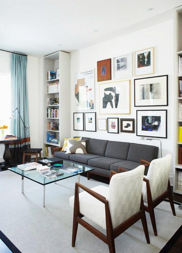 Gallery wall in gray living room with glass coffee table
