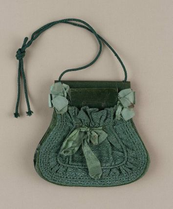 Bag. French, used in America, 1820-25. MFA, 49.996. 7 x 7.75 in. Silk compound weave, leather, silk plain weave ribbon, silk braided cord, cotton plain weave lining. Pocket-shaped green leather purse with envelope-style clasp at top, small leather envelope change purse beneath gathered silk fabric at front trimmed with bows, accordion pleated figured silk at sides and base, two cords knotted at top for carrying.