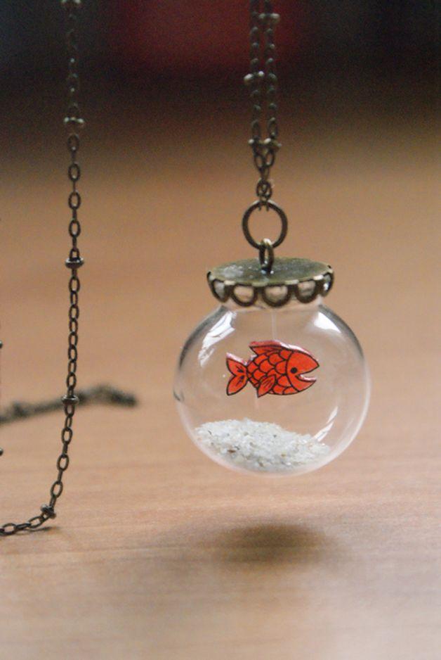 Poisson en plastique fou dans un globe en verre, capuchon et chaîne couleur bronze. Contient du sable en provenance du Finistère.  Les pièces de plastique sont dessinées, colorisées et découpées...