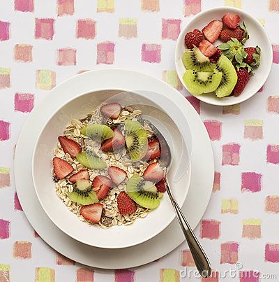 A white bowl of breakfast cereal topped with sliced strawberries and kiwi fruit on a patterned placemat.