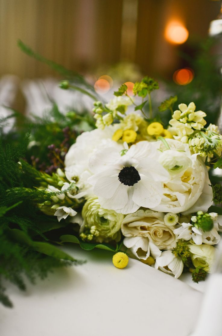 close up of bridesmaid bouquets made of white peony, pale yellow ranunculus, bupleurum, yellow stock, button chamomile, anemones, Amelia roses, white star of Bethlehem, white tulips, pale yellow stock and privet berry wrapped in cream satin ribbon