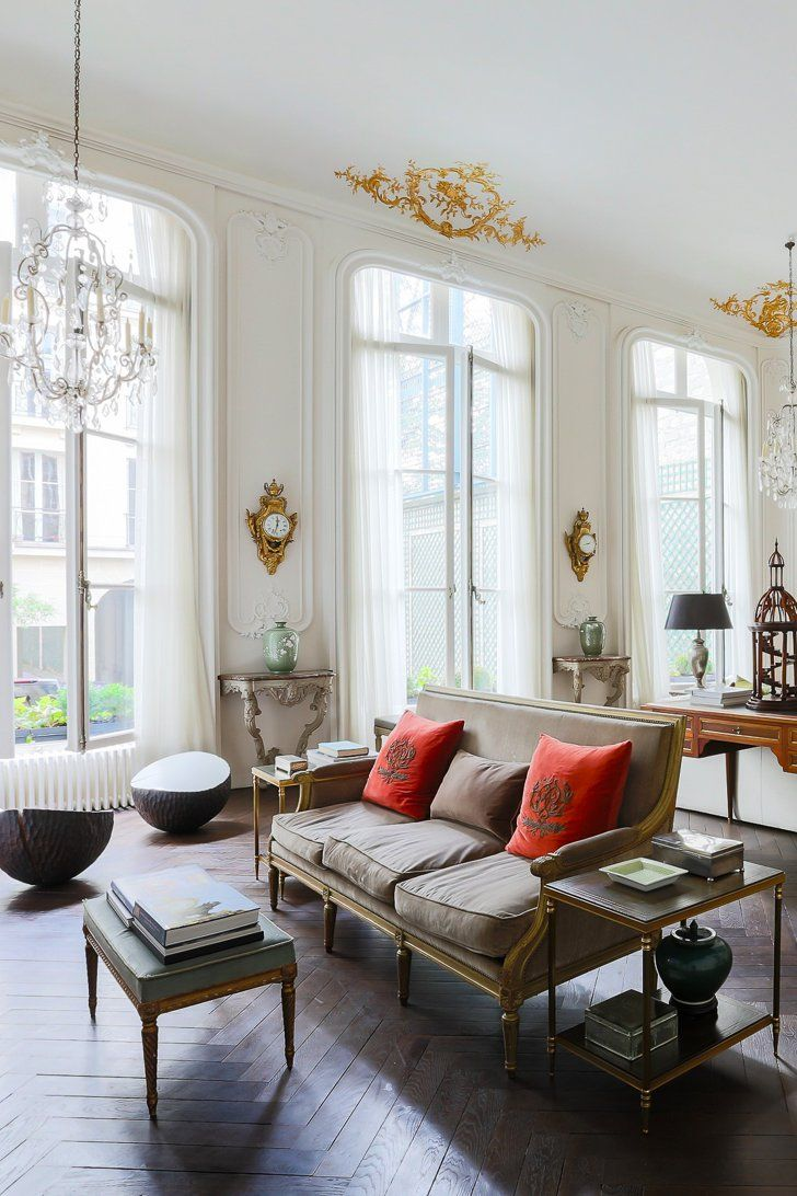 Stunning French living space with gold architectural details, a chandelier, large french patio doors and a love seat