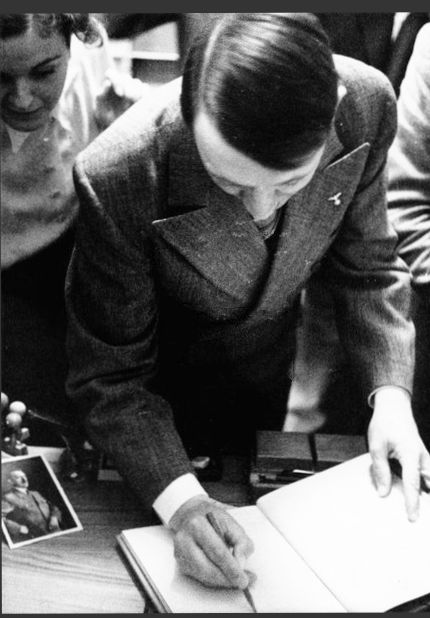 July 1939 and Hitler visits the photography shop of Heinrich Hoffmann in Munich. The sister of his lover is standing behind him and  hovering her hand over his back. This is Gretl Braun, whom Hitler nicknamed Kolibri (hummingbird).