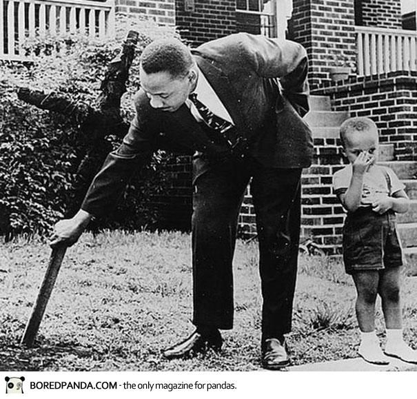 Martin Luther King with his son removing a burnt cross from their front yard, 1960