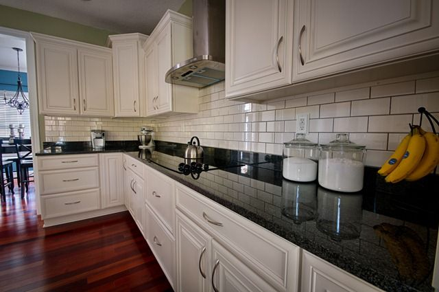 Kitchen Backsplash.  Imperial Bone Gloss subway tile from @The Tile Shop . black granite ivory cabinets wood floors