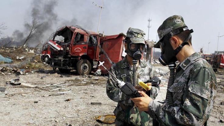 Des soldats de l'armée populaire de la Libération spécialisés dans les attaque chimiques effectuent des prélèvements sur la zone de l'explosion, le 16 août 2015 à Tianjin.