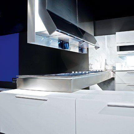 Cuisine Prima avec table en inox, hotte escamotable et meubles de rangement laqués blancs. Cuisine Binova